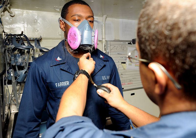 Файл:US Navy 110429-N-7326M-028 Boatswain's Mate 3rd Class Shaka K. Farrier dons a respirator as irritant smoke is released into the air as part of a re.jpg